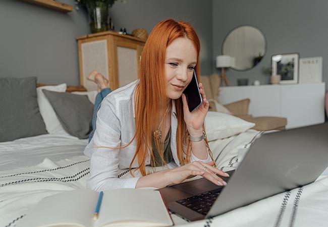 Falscher Microsoft-Anruf: Frau liegt mit Handy am Ohr vor ihrem Laptop. Bild: Pexels/Anthony Shkraba