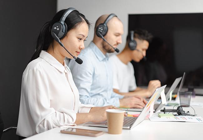 Microsoft-Anruf: Drei Personen mit Headset vor Computern. Bild: Pexels/Mikhail Nilov