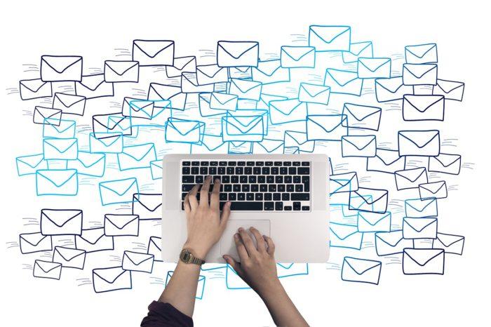 Menschliche Hände schreiben auf einer Tastatur. Im Hintergrund schweben viele Briefumschläge, die die Massen-E-Mails zur Pfändung symbolisieren. Foto: Pixabay