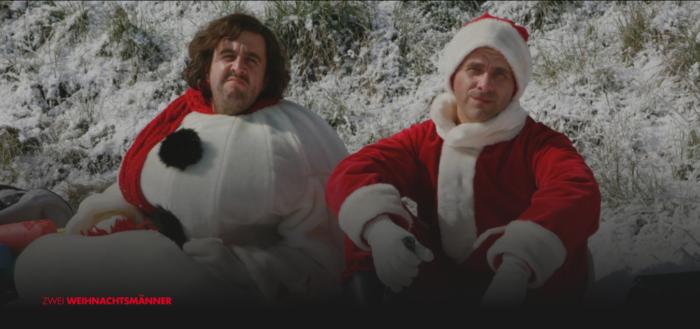 Ausschnitt aus dem Film Zwei Weihnachtsmänner: Zwei Männer - als Weihnachtsmänner verkleidet - sitzen mit ernsten Minen im Schnee. Der Film gehört zu unseren Empfehlungen für Weihnachtsfilme 2018. Foto: Screenshot