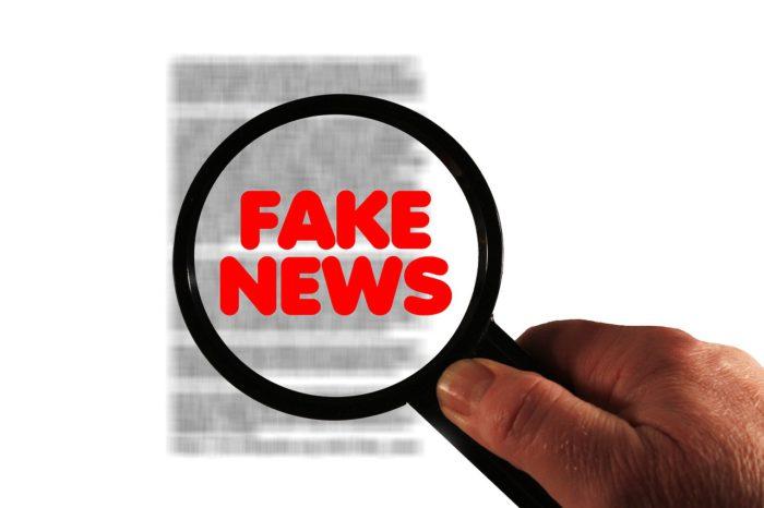 Eine Hand hält eine Lupe in der Fake News steht. Die Lupe zieht über ein Blatt Papier, was für den Facebook-Post steht. Foto. MaxPixel