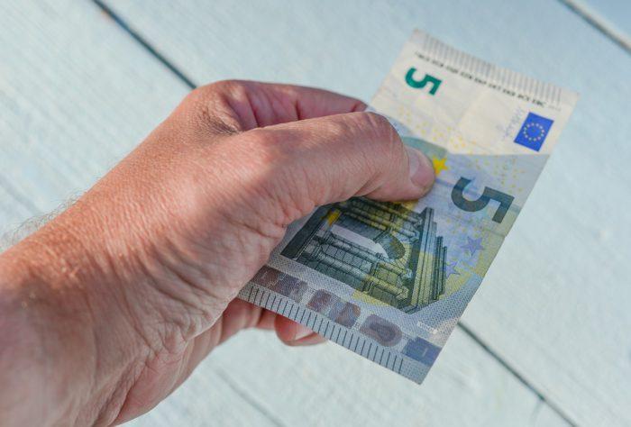 Eine Hand hält einen Fünf-Euro-Schein. Er symbolisiert den Schadensersatz an Qualcomm. Foto: Pixabay