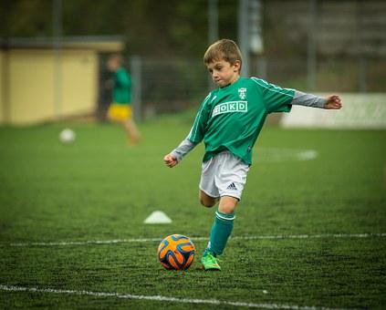 Ein kleiner Junge im grünen Trikot auf dem Fußballplatz setzt gerade an, einen Ball zu schießen. Foto: Pixabay