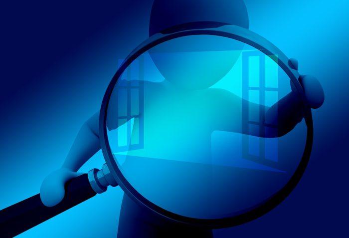 Eine große Lupe, gehalten von einer symbolischen Figur, überwacht das Windows-Fenster. Foto: Pixabay
