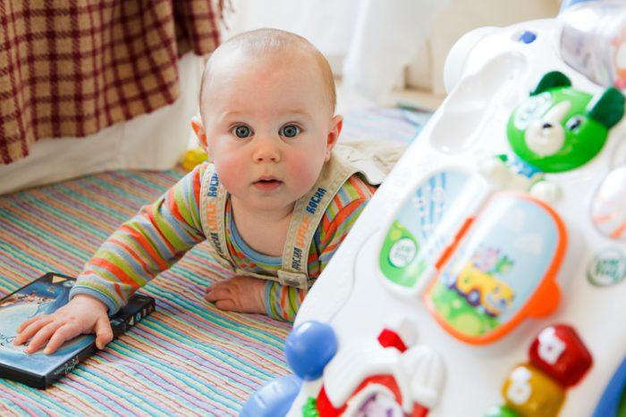 Ein Baby liegt auf dem Bauch auf einem Teppich. Es hat eine DVD in der Hand. Im Vordergrund ist ein Spielzeug zu sehen. Für die Kindergesundheit ist Bewegung wichtig. Bild: pixabay/PublicDomainPictures