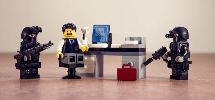 Lego-Männchen am Schreibtisch wird von zwei Lego-Männchen mit Waffe bedroht. Foto: Pixabay
