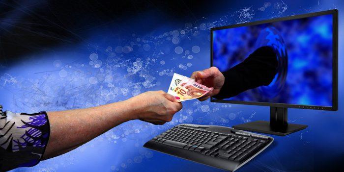 Das Bild zeigt einen Computer, aus dessen Bildschirm ein Arm kommt, der Geld des Besitzers fordert und erhält. Do funktioniert Trojaner Gozi. Foto: Pixabay