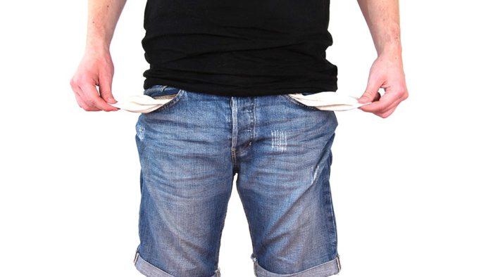 Zu sehen ist ein Mann und schwarzem T-Shirt und Jeans-Shorts. Er hat die Taschen der Hose nach Außen gestülpt, nichts ist darin. Er steckt in der Schuldenfalle. Bild: www.pixabay.com/1820796