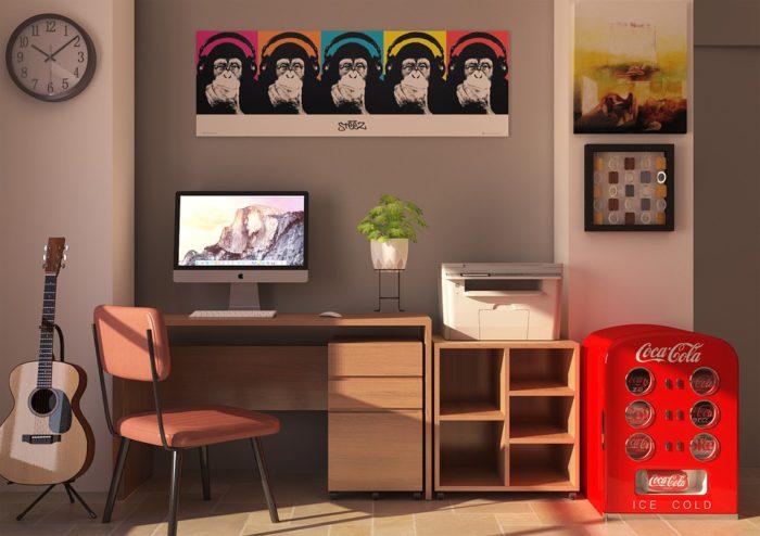 Zu sehen ist eine Wand, vor der ein Schreibtisch mit Computer, Drucker, Pflanze und Stuhl steht. Ein Bild mit einem Schimpansen hängt darüber, eine Uhr hängt links am Rand, darunter steht eine Gitarre. Der Bewohner hat einen Profi den Drucker installieren lassen. Bild: www.pixabay.com/Rani_Ramli