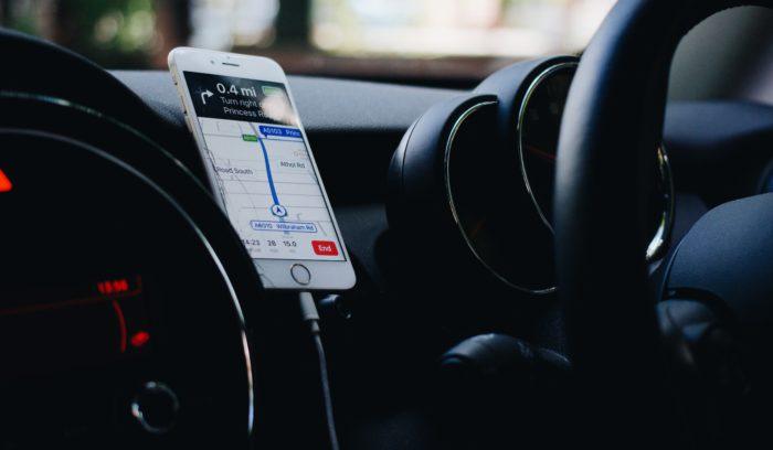 Zu sehen das Armaturenbrett eines Autos. In der Mitte ist eine Handyhalterung mit iPhone zu sehen. Die Karten-App von Apple ist aufgerufen. Mit iOS 13 Beta soll sie verbessert werden. Bild: www.unsplash.com / Samuel Foster