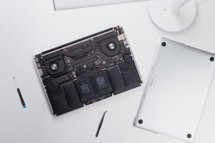 """Zu sehen ist die Reparatur eines MacBooks. Nach der Diagnose """"Display defekt"""" wurde das Gehäuse entfernt. Die Einzelteile und das Reparaturwerkzeug liegen auf einem weißen Untergrund. Bild: www.unsplash.com / Nikolai Chernichenko"""