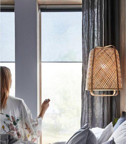 Zu sehen ist eine Frau mit Funkfernbedienung vor ihrem Schlafzimmerfenster. Sie steuert das smarte Rollo KADRILJ, das wie FYRTUR von IKEA ist. Bild: IKEA