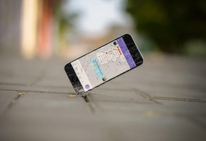 Zu sehen ist ein Handy, dass mit einer Ecke auf einen gepflasterten Boden fällt. Das Display ist kaputt. Besser ist: Handy-Schutzfolie anbringen. Bild: www.unsplash.com / Ali Abdul Rahman