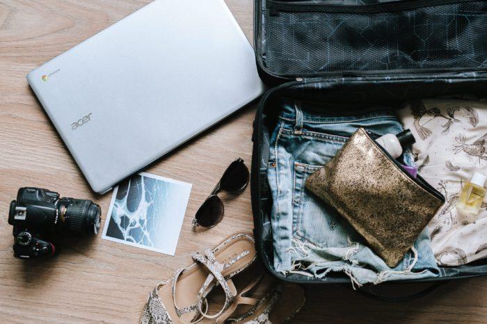 Zu sehen ist ein geöffneter Koffer. Er beinhaltet bereits einige Gegenstände, andere liegen noch neben ihm auf dem Boden. Eine Koffer-Packen-App hilft beim geordneten Packen. Bild: www.unsplash.com / Anete Lūsiņa