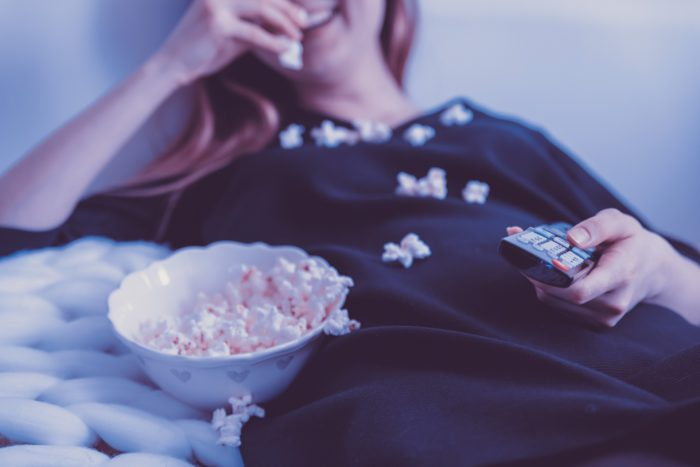 Zu sehen ist eine Frau, die es sich mit einer Schüssel Popcorn vor dem Fernseher gemütlich gemacht hat. Vodafone übernimmt Unitymedia bedeutet für sie, dass sie künftig das Angebot von Vodafone nutzen wird. Bild: www.unsplash.com / JESHOOTS-com