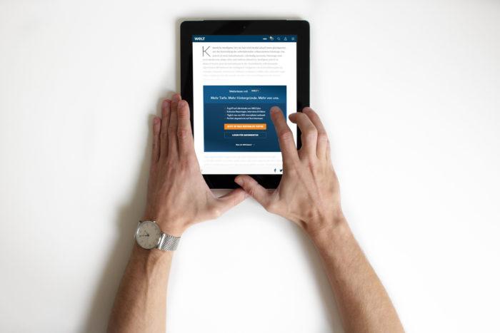 Zu sehen sind zwei Hände, die ein Tablet halten. Auf dem Tablet ist die Paywall der Nachrichtenseite von welt.de zu sehen. Bild: www.unsplash.com / NordWood Themes / Montage PC-SPEZIALIST