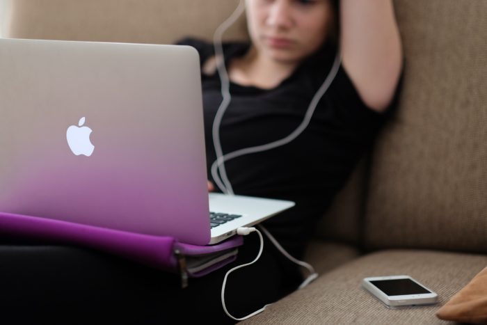 Zu sehen ist eine Frau auf dem Sofa, die gleichzeitig den Laptop nutzt, Musik hört und ihr Handy im Blick hat. Eine Folge der Internetnutzung. Bild: www.unsplash.com / Steinar Engeland