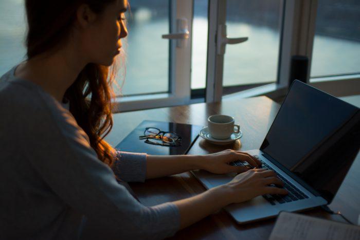 Zu sehen ist ein Bild in eher düsterer Stimmung, eine Frau arbeitet an ihrem Laptop. Schadet die Internetnutzung ihrer Konzentration? Bild: www.unsplash.com / Thought Catalog