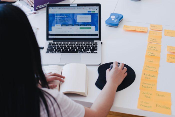 Zu sehen sind eine Frau am Laptop und eine Vielzahl von Notizzetteln daneben auf dem Tisch. Ob Sie eine professionelle Homepage erstellen möchte? Bild: www.unsplash.com / You X Ventures