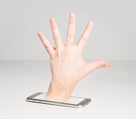 Eine Hand kommt aus einem Handy und bringt symbolisch Schadsoftware mit. Foto: Pixabay