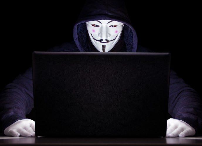 Das Foto zeigt einen Mann mit Maske und Handschuhen, der vor einem Laptop sitzt. Es symbolisiert den Angreifer, der das iPhone gehackt hat. Foto: PIxabay