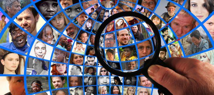 Köpfe von Menschen in Rahmen, vergrößert mit einer Lupe. Foto: Pixabay