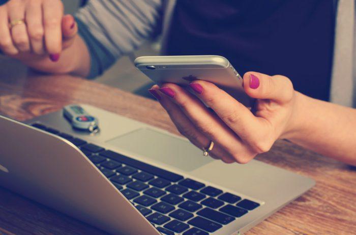 Das Bild zeigt eine Frau am Laptop mit Handy in der Hand. Ob ihre Handyrechnung falsch ist? Foto: Pixabay