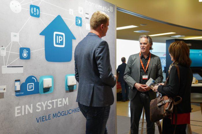 Messestand auf der IFA zum Thema Smart Home. Im Gespräch über IFA-Neuheiten sind zwei Männer und eine Frau. Quelle. Messe Berlin