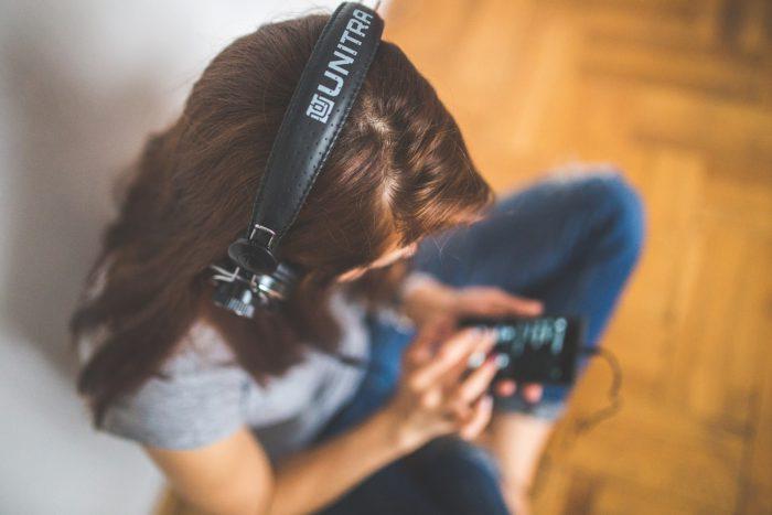 Eine Frau hört mit Kopfhörern über das Smartphone Musik. Bild: Pixabay / kaboompics