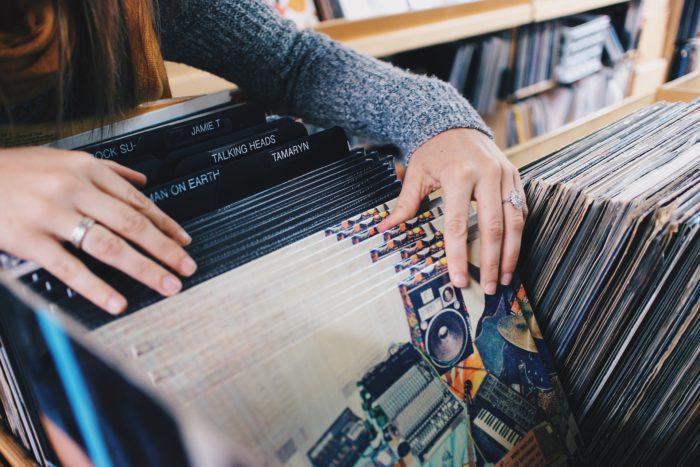 Eine Frau greift in eine Kiste mit Schallplatten – eine im Vergleich zu Spotify komplett anonyme Form Musik zu hören. Bild: Pixabay / Free-Photos
