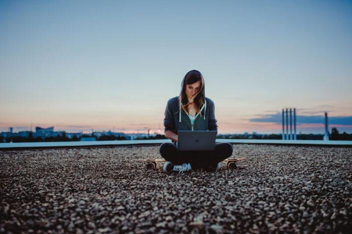 Eine Frau sitzt im Schneidersitz in der Mitte einen Hochhausdachs und nutzt einen Laptop auf Ihrem Schoß. Das Gerät nutzt Original-Software. Bild: Microsoft / Julia Müller