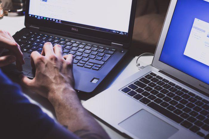 Zu sehen sind zwei Laptops, die ein Mann bedient. Hier geht es um Daten von PC zu PC übertragen - oder von Laptop zu Laptop. Bild: Unsplash / freestocks.org