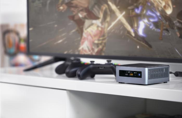 Zu sehen ist ein Sideboard mit Fernseher, Intel NUC Mini-PC und Gaming-Controllern. Bild: Intel