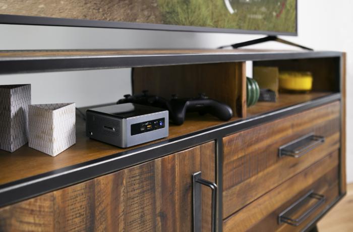 Zu sehen ist ein TV-Regal, auf dem ein großer Fernseher steht, während in einem Regalfach ein Intel NUC Mini-PC Platz findet. Bild: Intel