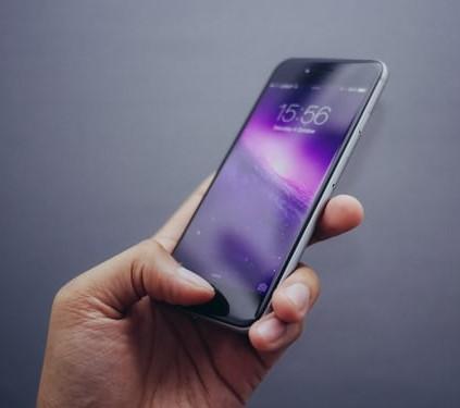 Hand hält Smartphone mit Lock-Screen. Handy-Betrug benötigt die Pin. Bild: Unsplash/@ultralinx