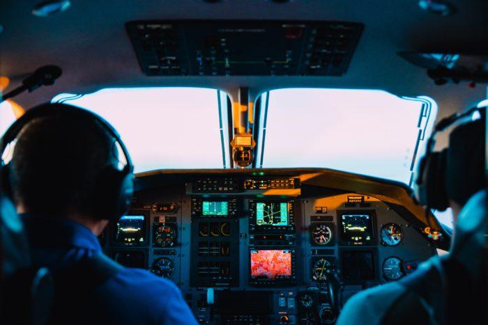 Zu sehensind zwei Piloten im Cockpit; wenn Passagiere den Flugzeugmodus vergessen, kann das die Funkverbindung der Piloten stören. Bild: Unsplash/Caleb Woods