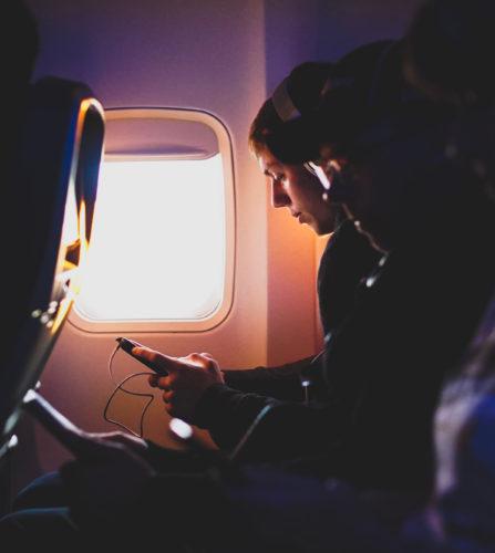 Ein junger Mann hört mit Handy und Kopfhörer im Flugzeug Musik. Ob er den Flugzeugmodus vergessen hat? Bild: Unsplash/Daniel McCullough
