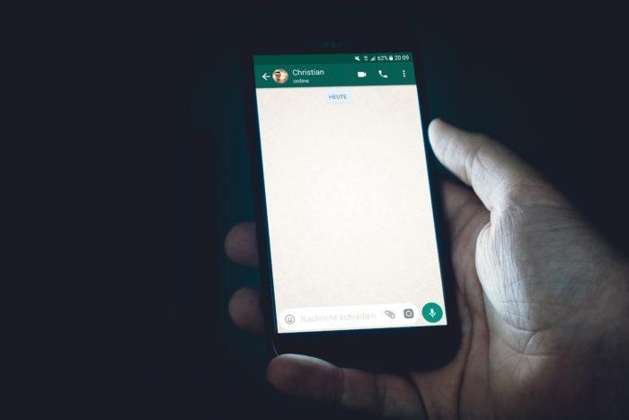 Leuchtendes Handydisplay vor dunklem Hintergrund: zeigt WhatsApp-Chat und den Status eines Kontakts.