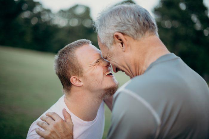Das Bild zeigt einen jungen Mann mit Downsyndrom, der einen älteren Mann anstrahlt. Er würde nach den Moderationsrichtlinien der App TikTok in seiner Reichweite beschränkt werden. Bild: Unsplash/Nathan Anderson