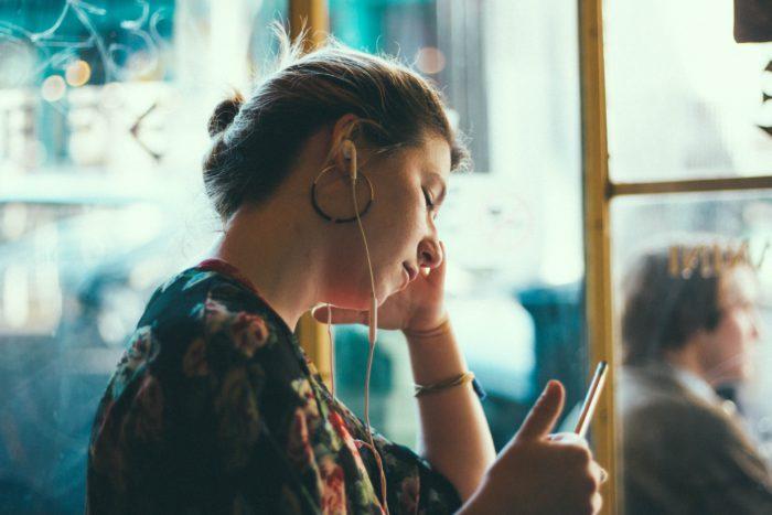 Eine Frau sitzt im Kaffee und hört mit ihren Kopfhörern Musik. Sie nutzt einen kostenlosen Musik-Streaming-Dienst. Bild: Unsplash/Siddharth Bhogra