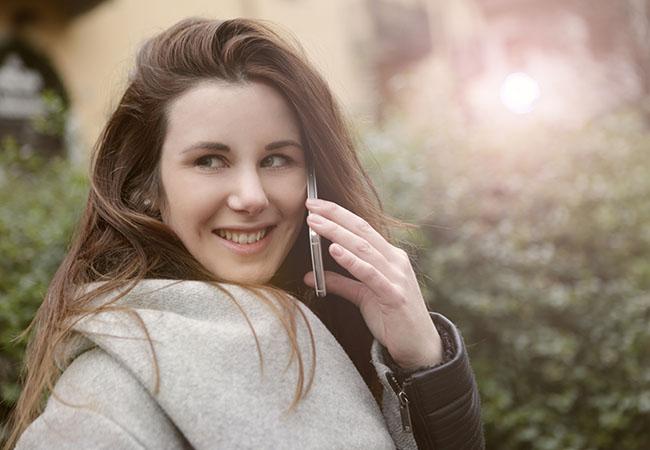 Basechat kostenlos: junge Frau, lächelt, mit Handy am Ohr. Bild: Pexels/Andrea Piacquadio