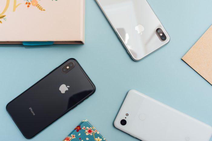 Zu sehen sind mehrere iPhones, die mit dem Bildschirm nach unten auf einer Fläche liegen. iOS 13.4 ist jetzt in der Beta-Version verfügbar. Bild: Unsplash/Arnel Hasanovic