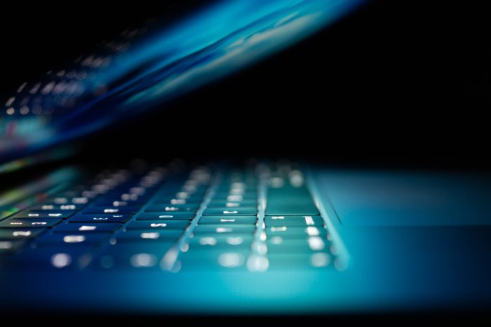 Zu sehen ist von der Seite ein fast zugeklappter Laptop, der Bildschirm hüllt die Tastatur in ein helles Licht. Der Besitzer benötigt Hilfe bei PC-Problemen. Bild: Unsplash/Philipp Katzenberger
