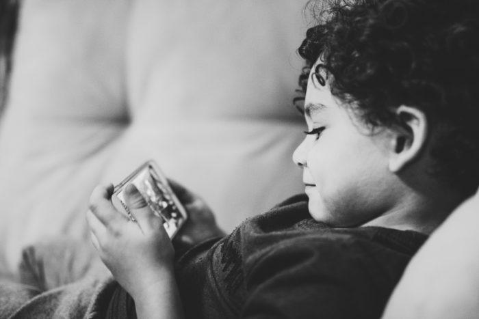 """Ein Kind liegt mit einem Smartphone auf dem Sofa. Wenn es heißt """"Schule zu wegen Corona!"""" müssen Eltern zu Mitteln greifen, die sie sonst eigentlich ausschließen würden: Ihre Kinder mit einem Smartphone oder Tablet unterhalten, damit sie aus dem Home Office arbeiten können. Bild: Unsplash/Diego Passadori"""