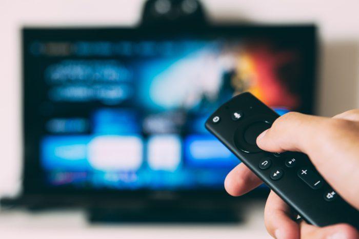 Zu sehen ist eine Hand mit Fernbedienung vor einem Smart-TV mit Streaming-Dienst. Die Streaming-Dienste drosseln aktuell die Video-Bitrate. Bild: Unsplash/Glenn Carstens-Peters