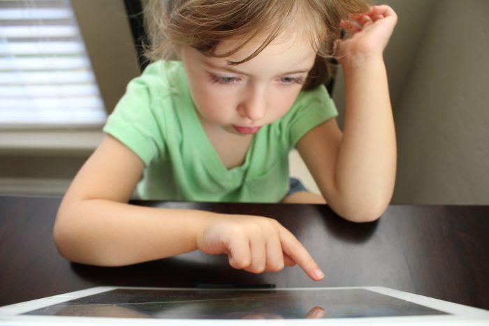 Zu sehen ist ein Mädchen mit einem Tablet. Es sieht sich das Coronavirus-Erklärvideo an. Bild: Unsplash/Hal Gatewood