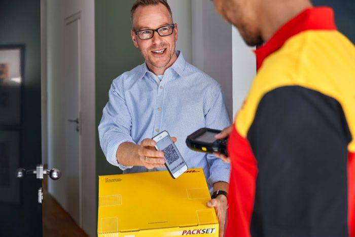 Zu sehen ist ein Paktebote, der einem Mann ein Paket zustellt. Über das DHL Live Tracking konnte der Mann die Position des Boten verfolgen. Bild: Deutsche Post DHL Group