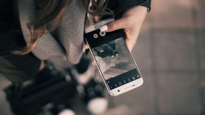 Zu sehen ist ein Teil einer jungen Frau, die ihr Handy nutzt. Ihre Bewegungsdaten werden dabei aufgezeichnet. Bild: Unsplash/by SHTTEFAN