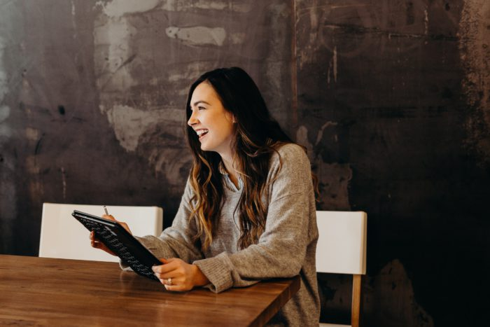 Zu sehen ist eine Frau, die mit einem Tablet am Tisch sitzt und an einer Zoom-Videokonferenz teilnimmt. Bild: Unsplash/Brooke Cagle