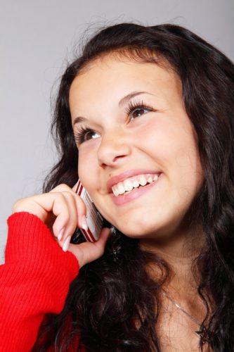 Lachendes Mädchen mit Handy telefoniert - Rufnummernportierung. Bild: Pixabay